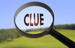 Clue. Magnifying glass with the word clue on blurred nature background. Searching clue concept Stock Photo