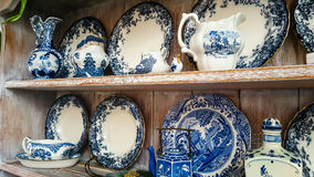 Clue and white plates and serving dishes. Vintage crockery displayed on wooden shelves in kitchen Stock Photos