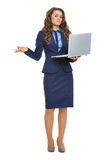 Clueless business woman with laptop shrugging shoulders Stock Photography