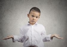 Clueless child boy with arms out asking what's problem stock photos