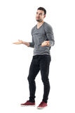 Clueless confused young man shrugging shoulders looking away. Full body length portrait isolated over white studio background Stock Images