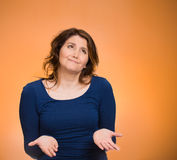 Clueless dumb woman. Closeup portrait dumb young woman, arms out asking what's problem, who cares so what, I don't know. Isolated orange background space to Royalty Free Stock Image