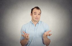 Clueless funny looking young man arms out asking what do I do now Stock Photo