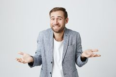 Clueless puzzled attractive man with beard, smiling broadly, having hesitation shrugging shoulders expressing. Clueless puzzled attractive and trendy man with stock image