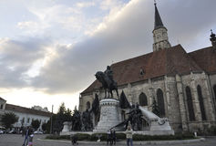 Cluj-Napoca RO, September 23th: Matei Corvin Monument and Church St Michael in Cluj-Napoca from Transylvania region in Romania Royalty Free Stock Photos