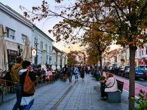 Cluj-Napoca, Romania - 14 ottobre 2018: La gente cammina sulla passeggiata davanti ad un caffè della via e si rilassa sui banchi  immagine stock