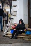 CLUJ NAPOCA, RUMÄNIEN - December 10, 2016: Den fattiga kvinnan med saknad fingrar sälja blommor på gatan Royaltyfri Fotografi
