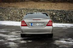 Cluj-Napoca Rumänien - mars 01,2018: Isolerad Mercedes-Benz E grupp-pseudonym W203, guld- metallisk färg, tonad kromprydnadblått Royaltyfri Fotografi