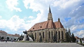 Cluj Napoca Unirii Square on a sunny day. Cluj-Napoca, Romania - 22 June 2015: Cluj Napoca Unirii Square with the St Michael Gothic Catholic Church and Matei stock footage