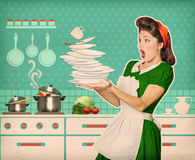 Clumsy attractive woman falling plates and dishes Royalty Free Stock Photos