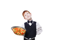 Clumsy inattentive little waiter drops pizza from tray. Clumsy little waiter drops tray with pizza while dreaming. Food falling down. Redhead child boy in suit Stock Photo
