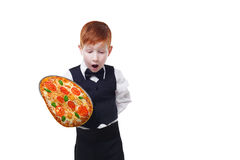 Clumsy little waiter drops tray serving pizza. Food falling down. Redhead child boy in suit shows inattentive waiter failure at white background Royalty Free Stock Photo