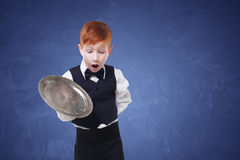 Clumsy little waiter drops tray serving something. Redhead child boy in suit shows inattentive waiter failure at blue background Royalty Free Stock Images
