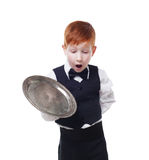 Clumsy little waiter drops tray serving something. Redhead child boy in suit shows inattentive waiter failure, isolated at white background Royalty Free Stock Image