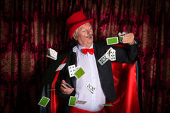 Clumsy magician. Mature magician on stage performing a magic trick with cards Stock Images