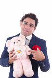 Clumsy man holding a teddy bear Stock Image