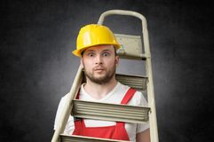 Clumsy worker with ladder. Clumsy construction worker standing with a ladder Royalty Free Stock Image