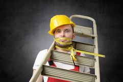 Clumsy worker with measure tape. Clumsy construction worker with ladder and measure tape Stock Photo