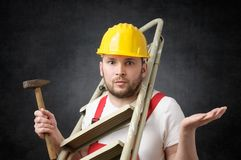 Clumsy worker with tools. Clumsy worker standing with ladder and hammer Stock Images