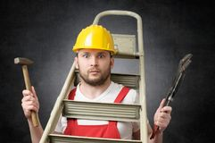 Clumsy worker with tools. Clumsy worker with ladder, hammer and pipe wrench Stock Images