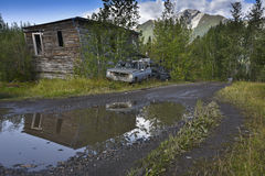 Clunker. In front of a hut reflects in a puddle Royalty Free Stock Photo