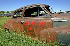 Clunkers for cash car. An old rusty car in a junkyard is used as an advertisement of paying cash for clunkers royalty free stock photos