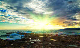 Cluodly sunset with setting sun among the storm clouds at sea off the coast of volcanic rock, Crete, Greece Royalty Free Stock Photo
