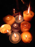 Cluster of candles. A cluster of different sized and coloured wax candles glowing with light Royalty Free Stock Photo