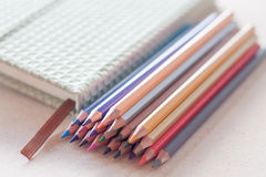 Cluster of colorful pencil crayons with green notebook Royalty Free Stock Photography