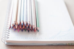 Cluster of colorful pencil crayons on spiral notebook Stock Images