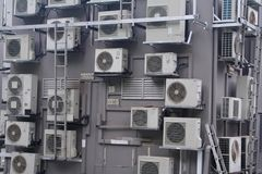 A cluster crowd of aircons. An over crowding of air conditioners on a buliding royalty free stock photo