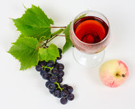 The cluster of grapes and apple lie near a wine glass with brand Stock Photo
