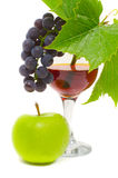 The cluster of grapes and apple lie near a wine glass with brand Stock Photography