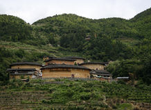 A cluster of Hakka Tulou homes in the valley backed by the mountain range Stock Photography