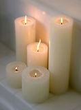 Cluster of lit candles on a ledge. Cluster of 5 lit candles of varying sizes on a ledge Royalty Free Stock Photography