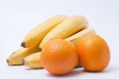 Cluster of ripe bananas and two oranges Stock Photo