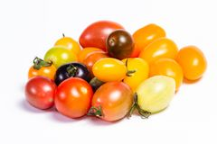 Colorful cherry tomatoes. Cluster of small cherry tomatoes in a variety of colors isolated on a white background Stock Images