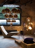 Cluster of Tom Dixon metallic pendant lights hanging in the Tom Dixon flagship store and showroom at Coal Drops Yard, Kings Cross. stock photo