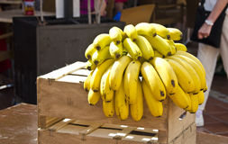 Cluster of yellow bananas on wooden box in the street Royalty Free Stock Photography