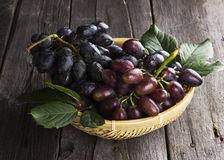 Clusters of dark grapes in wattled bowl on a wooden background Royalty Free Stock Image