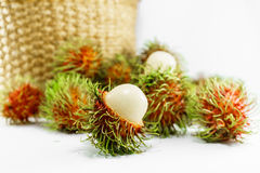 Clusters of fresh rambutan with basket in background. Thai fruit Royalty Free Stock Image