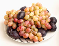 Clusters of grapes and plums on a plate Royalty Free Stock Photo