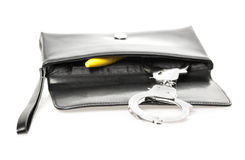 Clutch bag with explizit content. An open black clutch bag/purse with handcuffs and a yellow dildo Stock Images