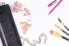 Clutch, cosmetics and makeup brushes on white background Stock Photography
