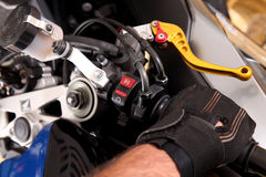 Clutch lever. Hand accelerating  a motorcycle with glove. Background Stock Photos