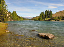 Clutha River - Wanaka, New Zealand. Morning view of the sparkling clear turquoise waters of the Clutha River where it starts at the outflow from Lake Wanaka. The Stock Photos