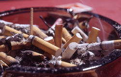 Cluttered ashtray. Close view of cigarette butts in ashtray Stock Images