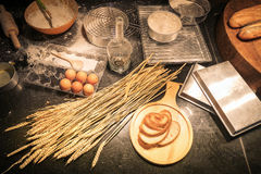 Cluttered kitchen by a beginner of homemade bakery. With baking ingredients as flour, rolling pin, whisk, egg shells mesh, and plastic molds for baking. Pile Stock Photos