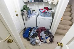 Cluttered Messy Laundry Room with Piles of Clothes stock photography