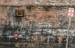 Cluttered Old Brick Wall Background with Graffiti and Sign 2 Royalty Free Stock Photo